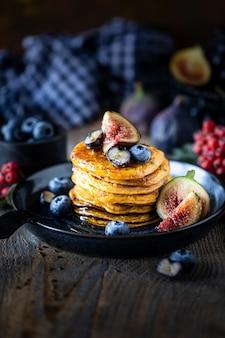 Pompoenpannenkoeken met stroop of honing, lijnzaad, vijgen, bosbessen in een donker bord op de tafel