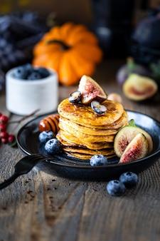 Pompoenpannenkoeken met stroop of honing, lijnzaad, vijgen, bosbessen in een donkere plaat op tafel, selectieve aandacht, kopie ruimte
