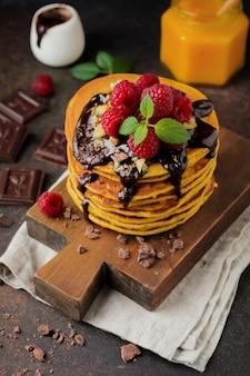 Pompoenpannenkoekjes met verse frambozen, chocolade en walnoten op donkere steen of beton.