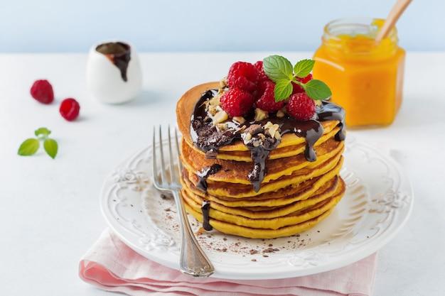 Pompoenpannenkoekjes met verse frambozen, chocolade en walnoten op lichte steen of beton.