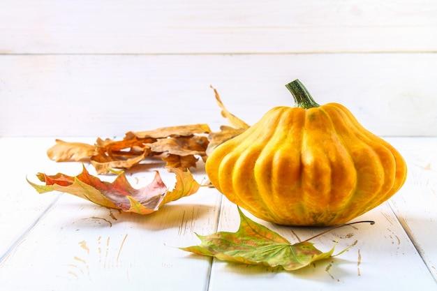 Pompoenpasteitjespan en esdoorn gele bladeren op een witte houten tafel. herfst oogst.