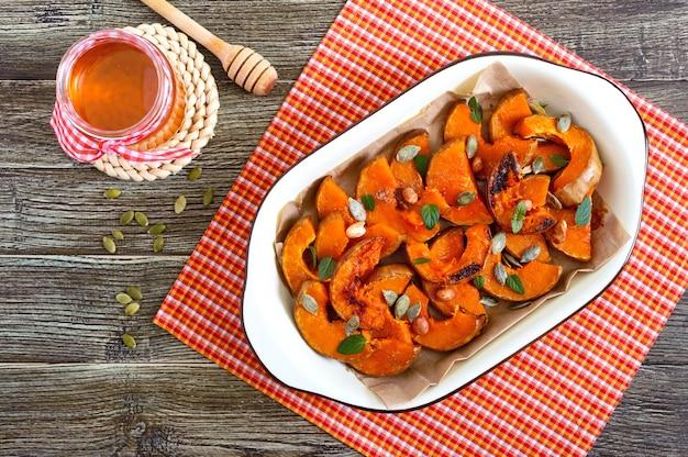 Pompoenplakken gebakken in de oven met honing, noten, kaneel, zaden, munt. stukjes pompoen die op het bakpapier in een kom liggen. gezond eten, dessert voor fijnproevers. traditionele herfstsnack in hongarije