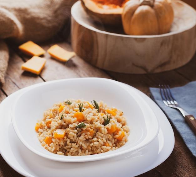 Pompoenrisotto, recept met rijst en pompoen op rustieke tafel met ingrediënten.