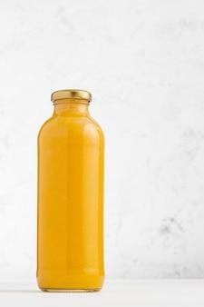 Pompoenroomsoep in glazen fles met lichte achtergrond en kopie ruimte