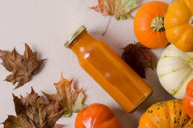 Pompoensap in een fles close-up op een herfst achtergrond met esdoorn bladeren,
