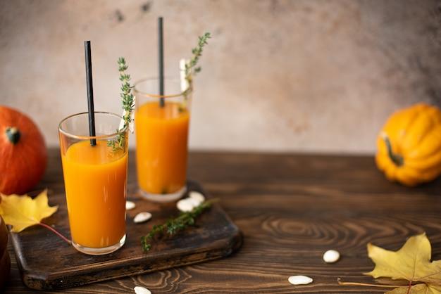 Pompoensap in een fles en glas op een houten tafel