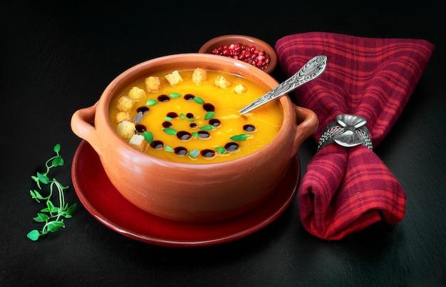 Pompoensoep geserveerd in keramische kom met pompoenolie