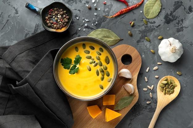 Pompoensoep in diepe kom met zaden, peterselie, knoflook, laurier, kruiden, paprika op grijze tafel met servet en lepel, bovenaanzicht