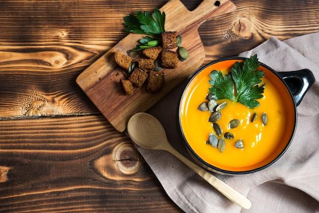 Pompoensoep in een kom met zaden en peterselie op een houten tafel