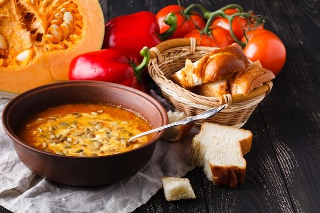 Pompoensoep in kom op rustieke lijst met brood