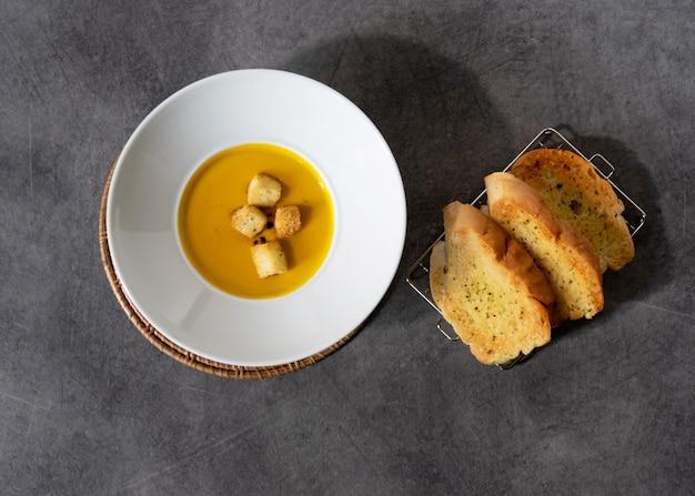 Pompoensoep met croutonsbrood in het brood van het plaatknoflook op steenachtergrond met lege copyspace