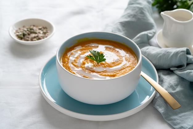 Pompoensoep met kokosmelk, vegetarische schotel, gezond en dieetvoedsel op wit tafelkleed