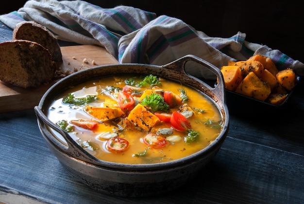 Pompoensoep met tomaten en kruiden in een rustieke stijl.