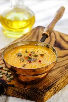 Pompoensoep met wortelpuree met zaden, roze peper en olijfolie