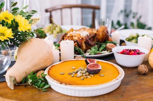 Pompoentaart op feestelijke tafel met voedsel