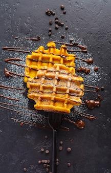 Pompoenwafels met chocolade en suikerpoeder dat op vork op donkere oude lijst wordt geregen. bovenaanzicht