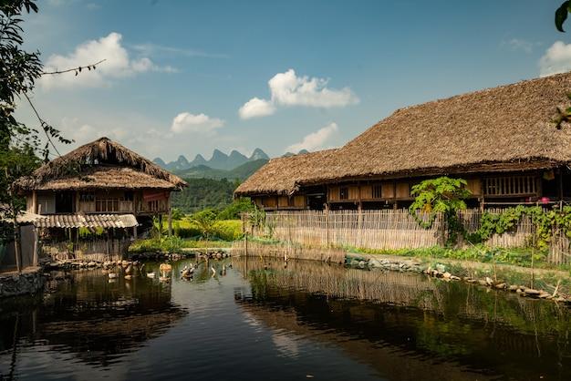Pong met een houten dorpsgebouw ernaast onder een blauwe lucht