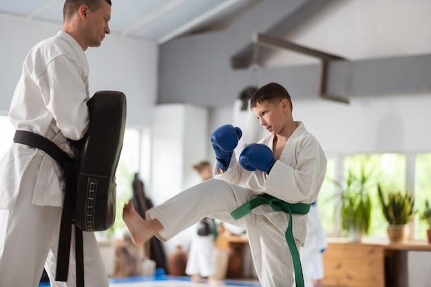 Ponsen oefenen. donkerharige actieve jongen met beschermende handschoenen die zijn stoten oefent