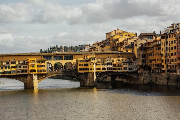 Ponte vecchio met rivier de arno in zonnige lentedag in florence, italië.