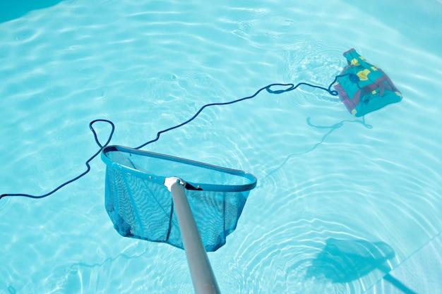 Poolschuimspaan en schoonmakende robot in zwembad