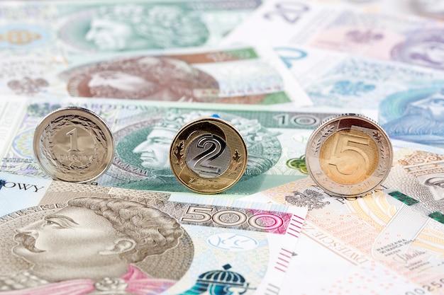 Poolse zloty-muntstukken op de achtergrond van poolse bankbiljetten