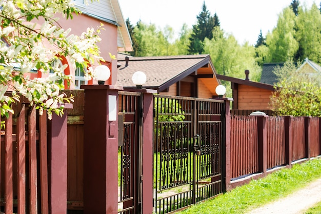 Poort, hek en lente natuur. kleurrijke de lenteachtergrond, huisingang, beteugelen beroep.