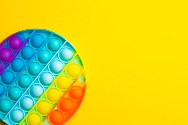 Pop het anti-stress op een gele ondergrond. moderne speelgoed. speelgoed voor kinderen. siliconen spel. autisme.