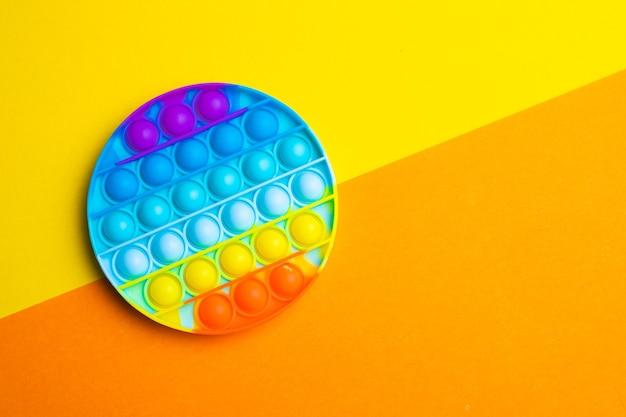 Pop it anti-stress op een gekleurd oppervlak. moderne speelgoed. speelgoed voor kinderen. siliconen spel. autisme.