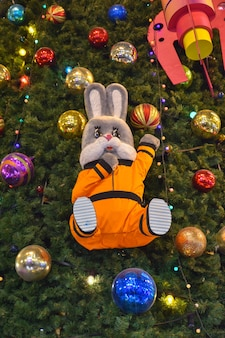 Pop op kerstboomhaas in ruimtepak op kerstboom