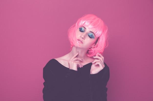 Pop stijl vrouw in een roze pruik en zwarte kleren poseren op een camera geïsoleerd.