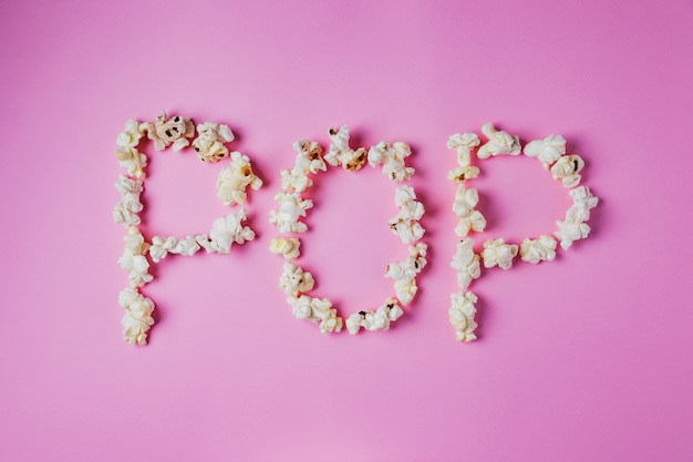 Pop word geschreven met popcorn op roze oppervlak