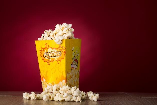 Popcorn die op rode achtergrond wordt geïsoleerd