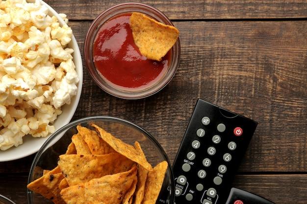 Popcorn en diverse snacks, tv-afstandsbediening op een bruine houten achtergrond. concept van films kijken thuis. uitzicht van boven