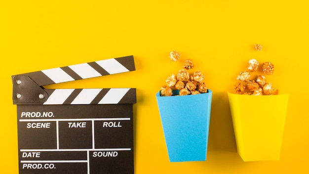 Popcorn en filmklapper op gele tafel.