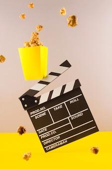 Popcorn en filmklapper op kleurrijke tafel.