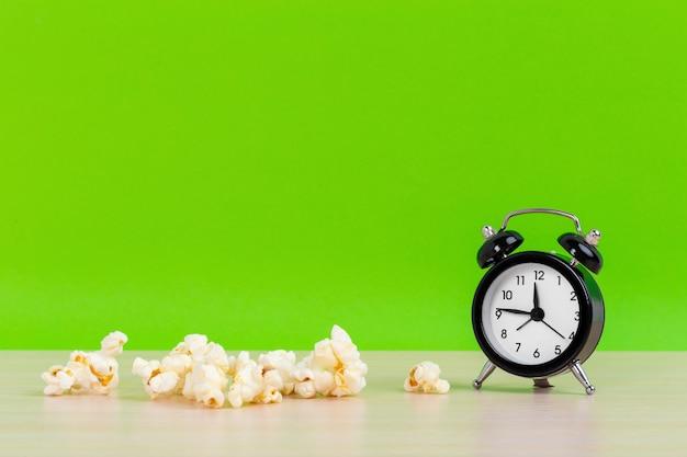 Popcorn en kleine wekker op minimale creatieve conceptruimte van het pastelkleur groene oppervlakte ruimte voor exemplaar