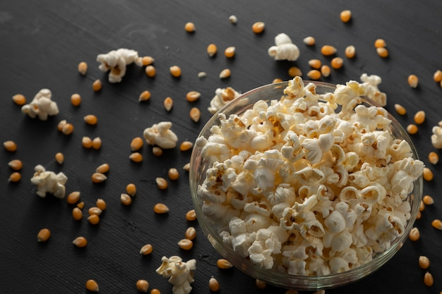 Popcorn en popcorn in een kom liggend op de vintage zwarte tafel