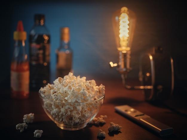 Popcorn en tv-afstandsbediening in het donker