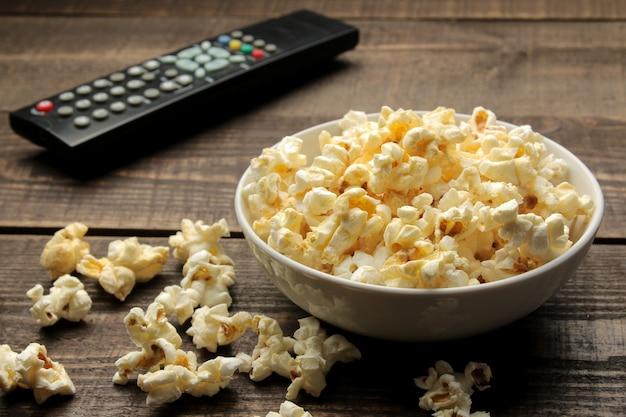 Popcorn en tv-afstandsbediening op een bruine houten tafel, concept van het kijken naar films thuis.