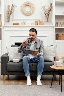 Popcorn eten en een afstandsschot van een digitaal apparaat gebruiken Premium Foto