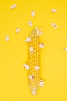 Popcorn explodeert op de maïskolf op een gele kleur