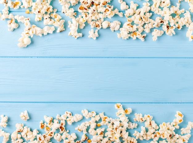 Popcorn horizontale banner. kernels die in vorm van kader op blauwe houten achtergrond liggen.