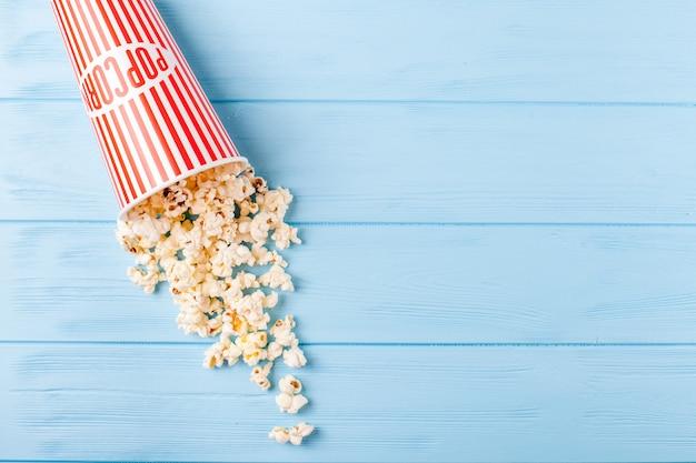 Popcorn horizontale banner. rode gestripte document kop en pitten die op blauwe houten achtergrond liggen.