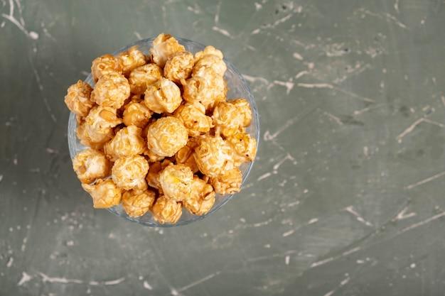 Popcorn in een glas op een groene tafel
