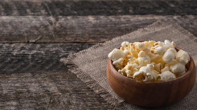 Popcorn in een houten kom. ruimte voor tekst