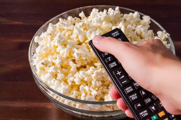 Popcorn in glazen kom en afstandsbediening