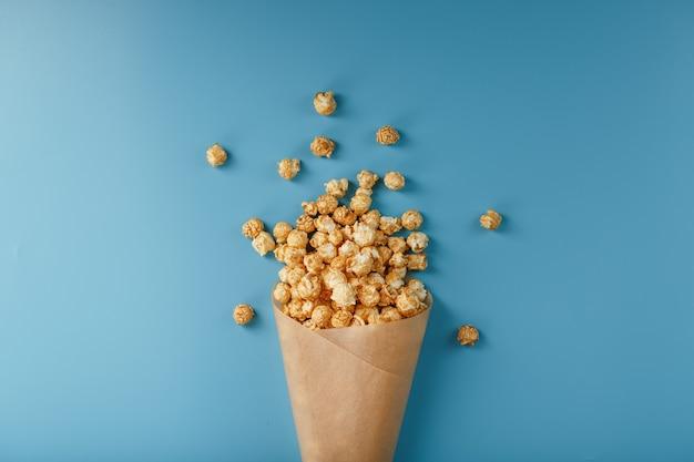 Popcorn in karamelglazuur in een papieren envelop op een blauw.