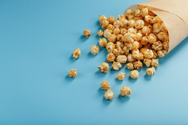 Popcorn in karamelglazuur in een papieren envelop op een blauwe achtergrond.