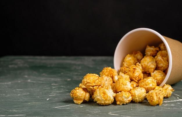 Popcorn in kartonnen beker op groen oppervlak