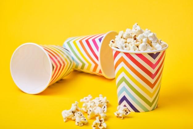 Popcorn in papieren bekers op gele achtergrond